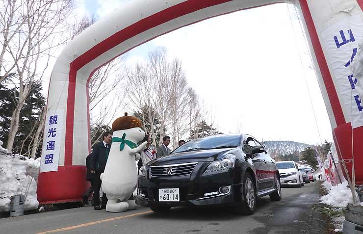 志賀高原の観光PRキャラクター「おこみん」らに見送られながら陽坂ゲートを通る車両