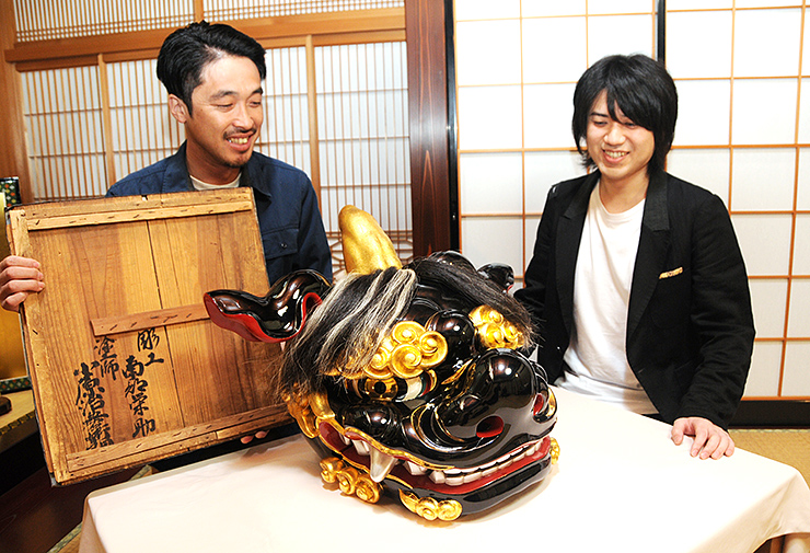 修復を終えた獅子頭を前に笑顔を見せる高桑さん(左)と小原さん
