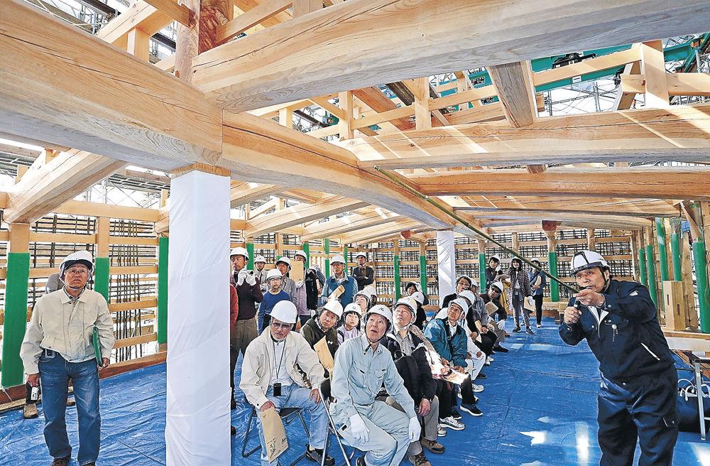 正確に木材がつなぎ合わさった柱やはりに見入る参加者=金沢城公園