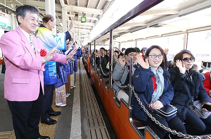 大野黒部市長(左)ら関係者に見送られ出発するトロッコ電車の乗客=黒部峡谷鉄道宇奈月駅