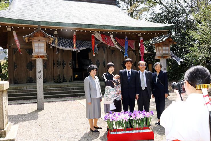 こいのぼりが飾られた社殿の前で記念撮影する家族