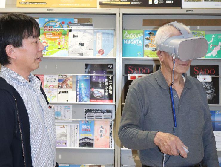 ゴーグルを着けVR映像を体験する市民(右)=佐渡市の両津港佐渡観光案内所