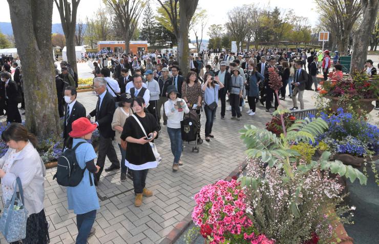 多くの来場者でにぎわう「信州花フェスタ」主会場の県松本平広域公園。花壇の前では色とりどりの草花を写真に収める姿が目立った=25日
