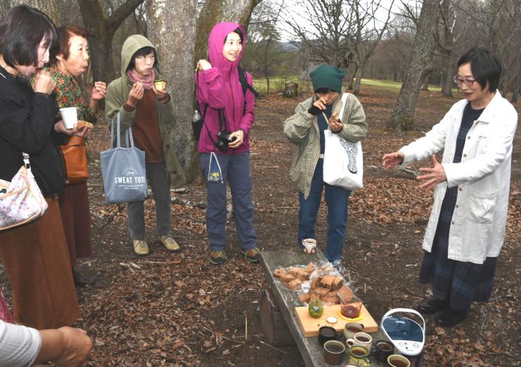 清水さん(右)からドングリ粉を使ったパンや茶の説明を受けるメンバーら