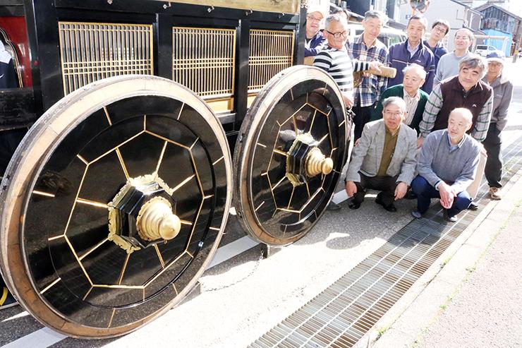 修繕が終わった車輪を見つめる南上野町の住民=小矢部市石動町