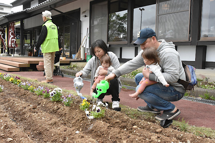 千曲市姨捨観光会館前に花の苗を植えて水をやる家族連れ