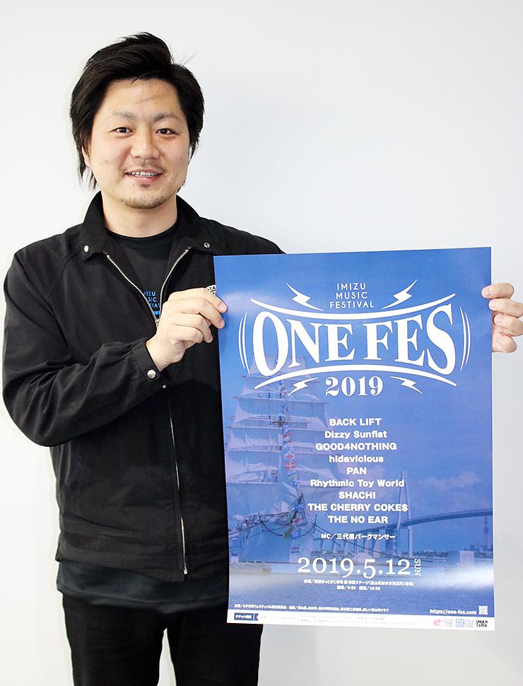野外音楽イベント「ONE FES 2019」のポスターを持つ加治さん