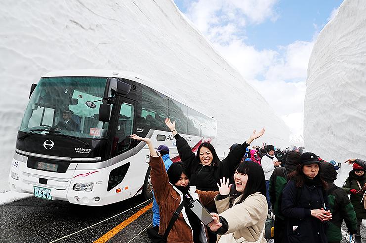 雪の壁をバックに、ポーズを決めて自撮りする観光客=立山・雪の大谷