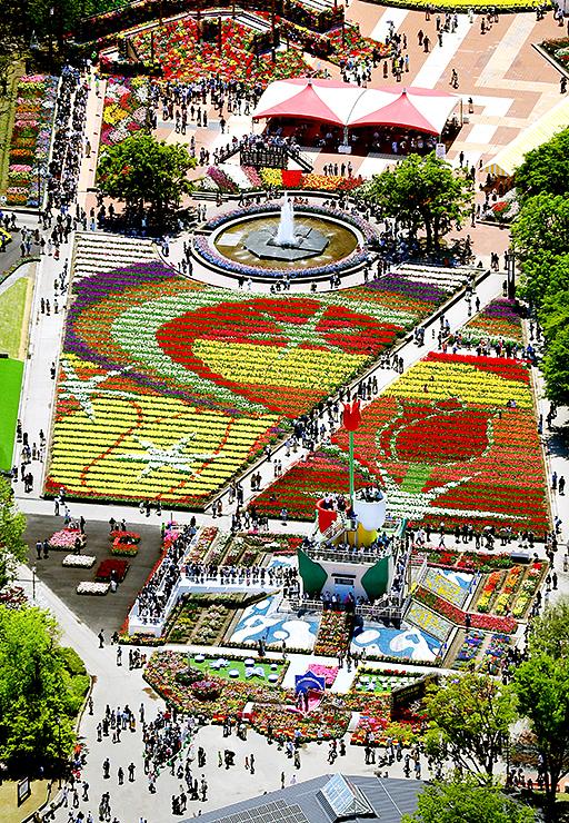 上空のヘリコプターからは、大花壇に色鮮やかな地上絵が浮かび上がり、大勢の人たちがタワーの上から眺めている様子が見られた(チャーターヘリから撮影)