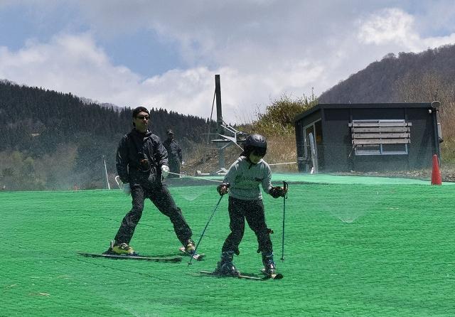 人工ゲレンデでスキーを楽しむ家族連れ=5月2日、福井県大野市南六呂師の六呂師高原スキーパーク