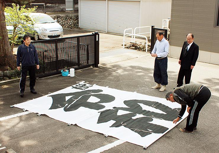 糸目を取り付けるため「令和」と大書された凧を広げる枇杷首自治会の関係者=射水市枇杷首
