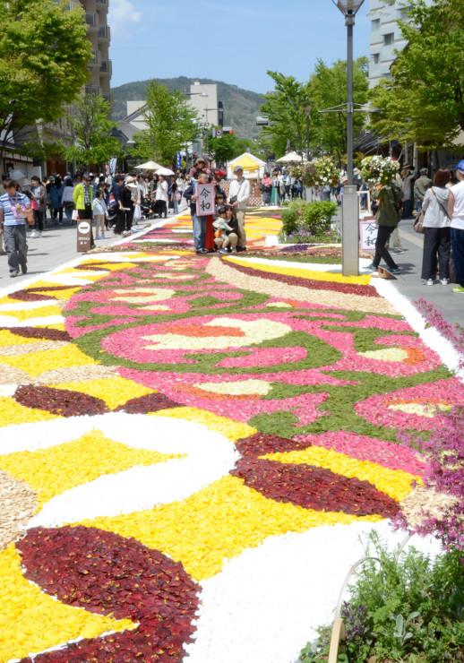 「令和」の額を手に、色鮮やかな「花キャンバス」の中で記念撮影をする人たち
