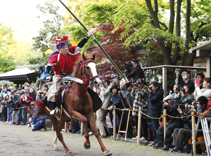 大勢の見物客が見守る中、疾走する馬から矢を射る男性=下村加茂神社