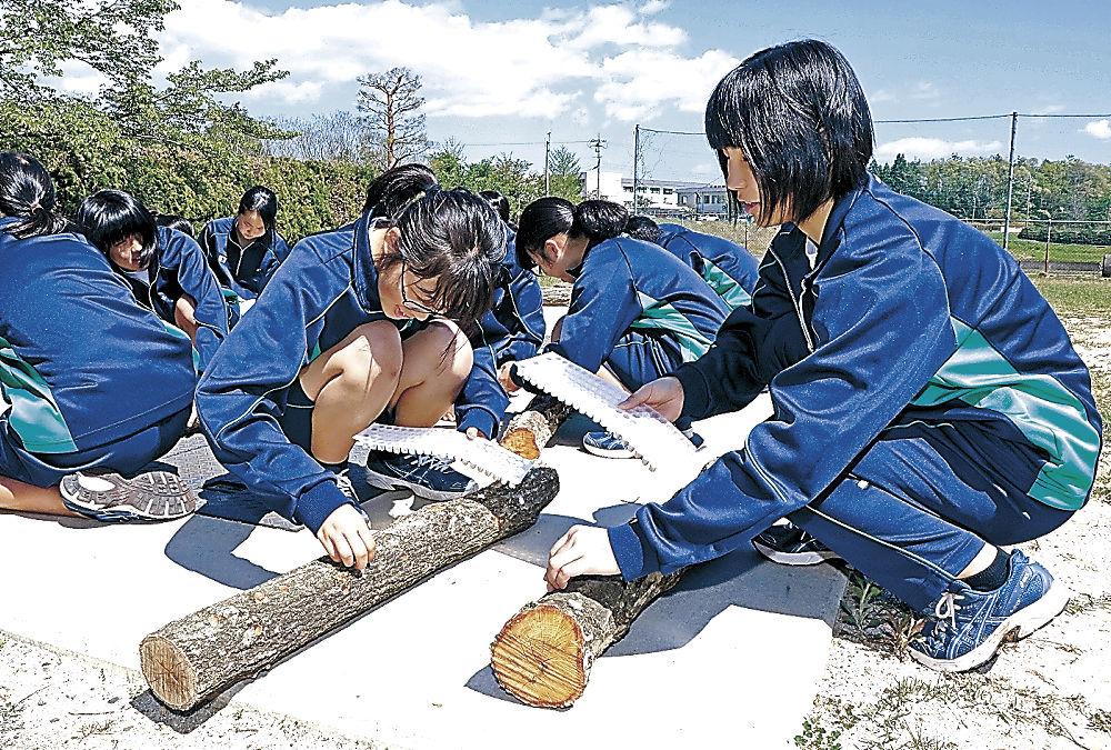 シイタケの菌を植える生徒=穴水高