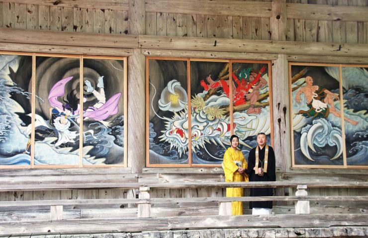 「イケメン絵巻」を背に立つアーティストの木村了子さんと国上寺の山田光哲住職=燕市
