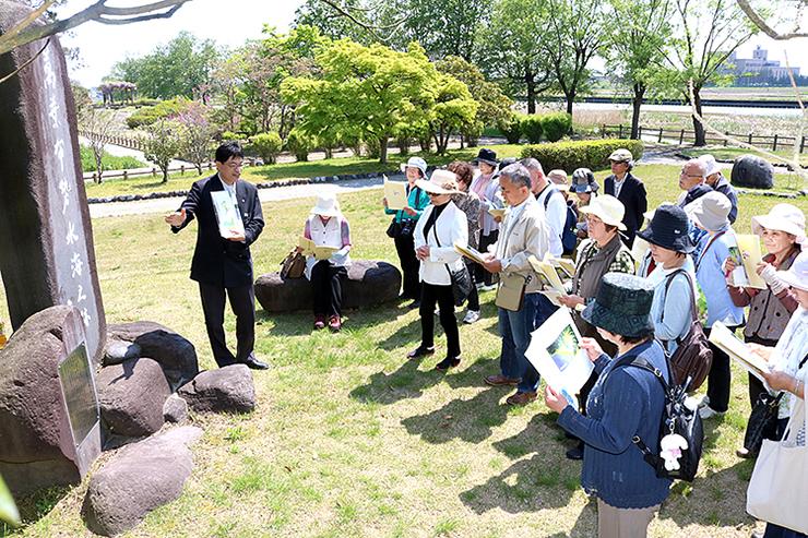 十二町潟水郷公園を訪れ、小谷課長補佐(左)の解説で家持ゆかりの碑を見学する美術協会員