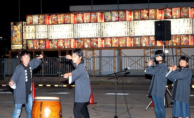 点灯した田楽あんどんの前で太鼓や笛を演奏する子ども=あんどん広場