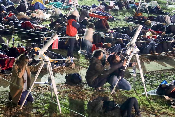 体望遠鏡を使ったり、寝転がったりして星空を眺める参加者たち