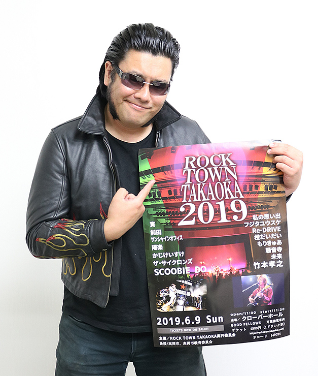 ポスターを手に持ち、PRする村井委員長