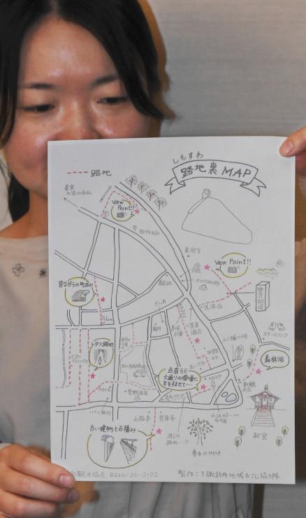 「しもすわ路地裏MAP」を手にする地域おこし協力隊員の唐戸さん