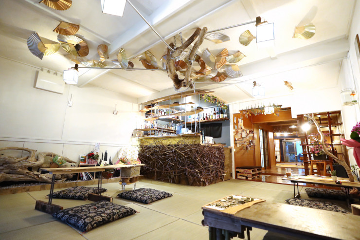 流木や扇子などで飾ったカフェの室内