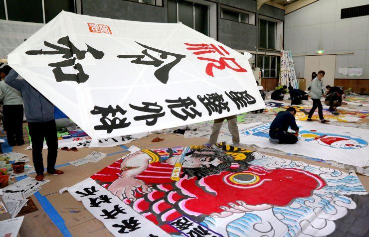 「令和」の文字が書かれた凧も作られている絵付け作業=13日、長岡市中之島