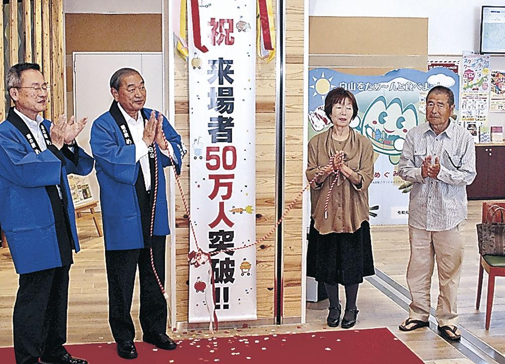 来場者50万人突破を祝う林さん(右)と禮子さん(右から2人目)=白山市の道の駅「めぐみ白山」