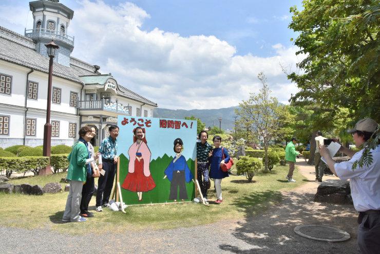 国宝になる旧開智学校校舎の前で、開智小児童が作った「顔出しパネル」を利用して記念撮影する見学者ら=18日、松本市開智2