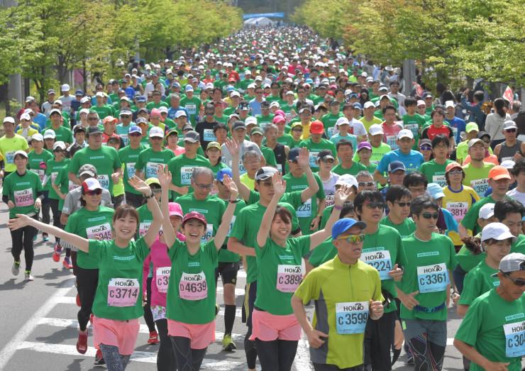 一斉にスタートし、新緑の中を駆け抜ける軽井沢ハーフマラソンの出場者=19日、軽井沢町