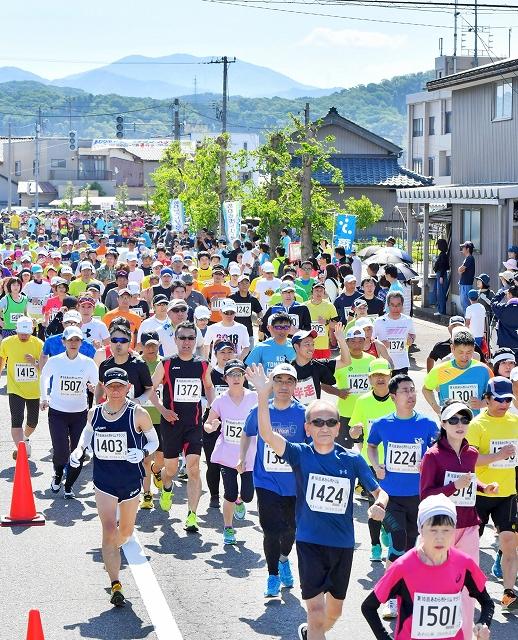 初夏の日差しを浴びながらスタートするランナー=5月19日、福井県あわら市市姫2丁目