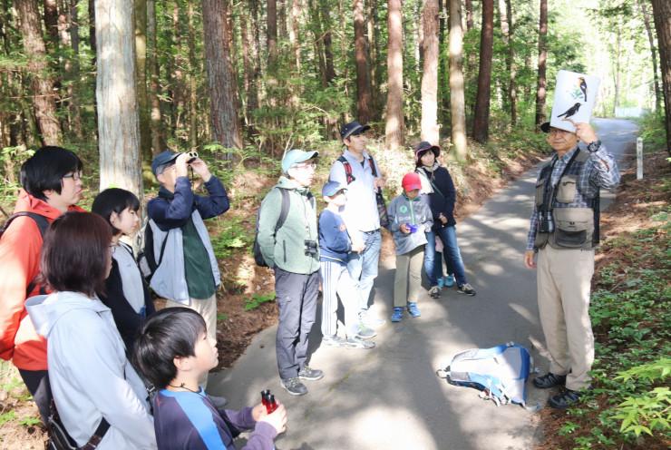 渡辺さん(右)の案内で野鳥を観察する参加者