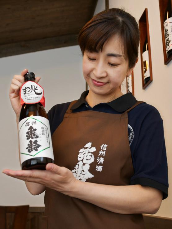受賞した「信州亀齢 山恵錦 純米吟醸」を手にする岡崎社長の妻で杜氏の美都里さん