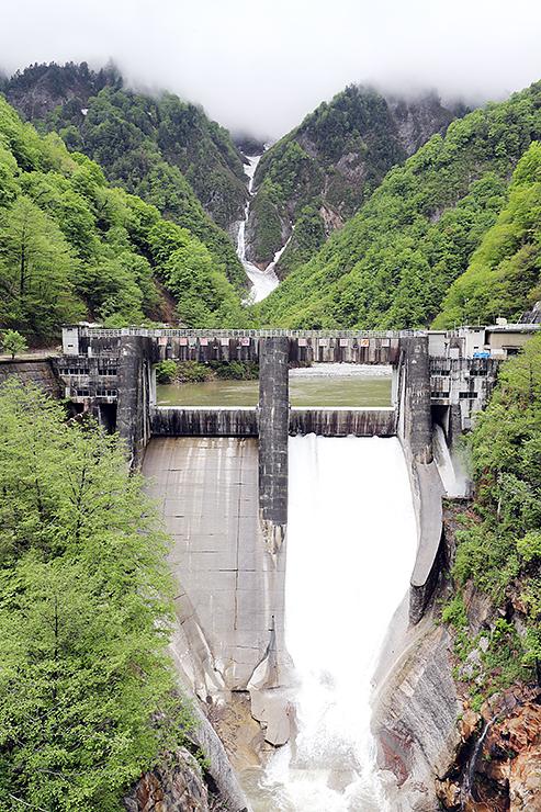 新緑と雪の残る山に囲まれた仙人谷ダム=仙人谷