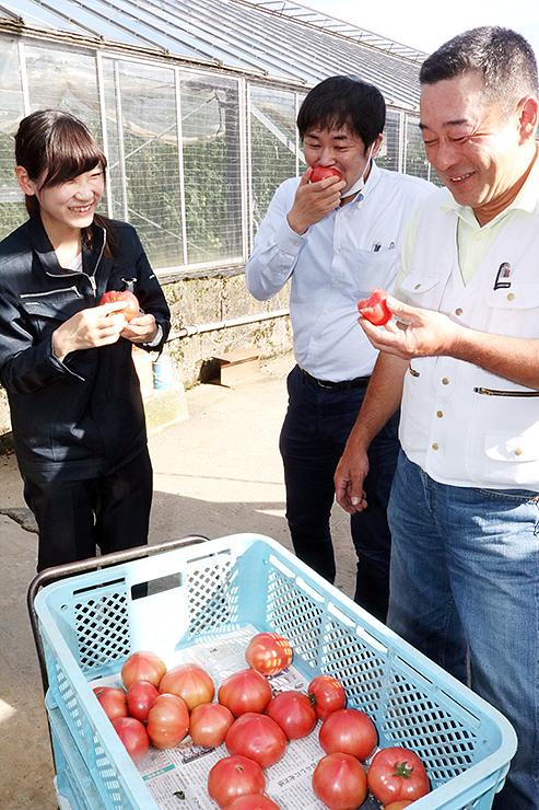 しんきろうトマトを試食する種田部会長(右)ら参加者