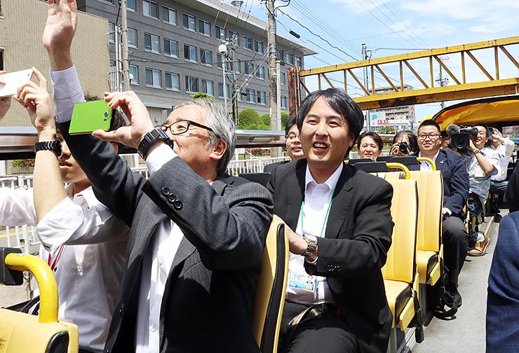 まちなかを走るバスに乗り、景色を楽しむ関係者ら=富山市赤江町交差点付近