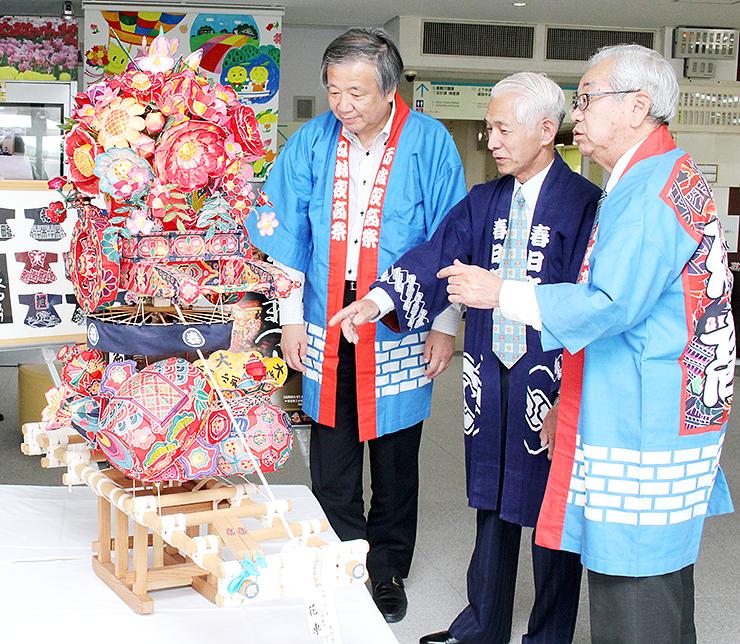 渡辺さん(中央)が製作し、市役所玄関に飾られたミニ行燈