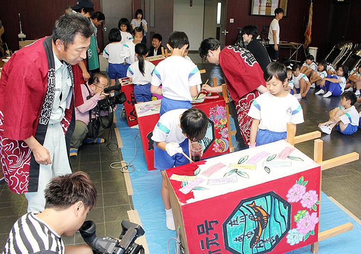 会員らの指導でトッペ行燈に色を付ける児童=庄川コミュニティ防災センター
