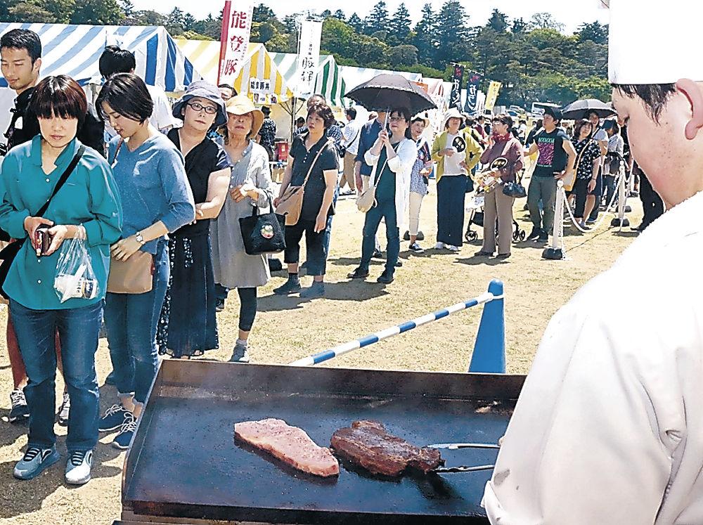 能登牛のステーキを求めて行列をつくる来場者=金沢市のしいのき緑地