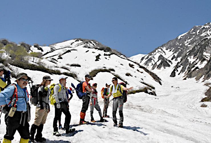 青空の下、涼風を感じながら白馬大雪渓でトレッキングを楽しむ人たち