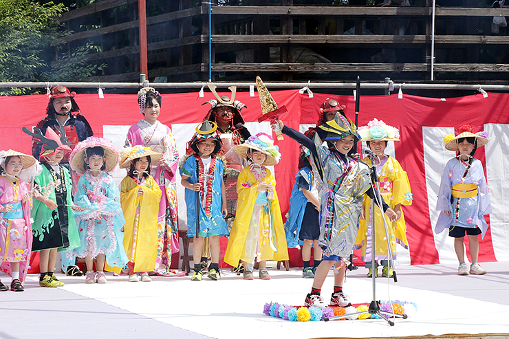 手作りしたよろいや着物を身に着けてポーズを取る児童=入城の門広場