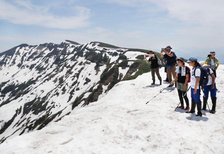 雪が残る山頂で景色を楽しむ登山客=26日、守門岳