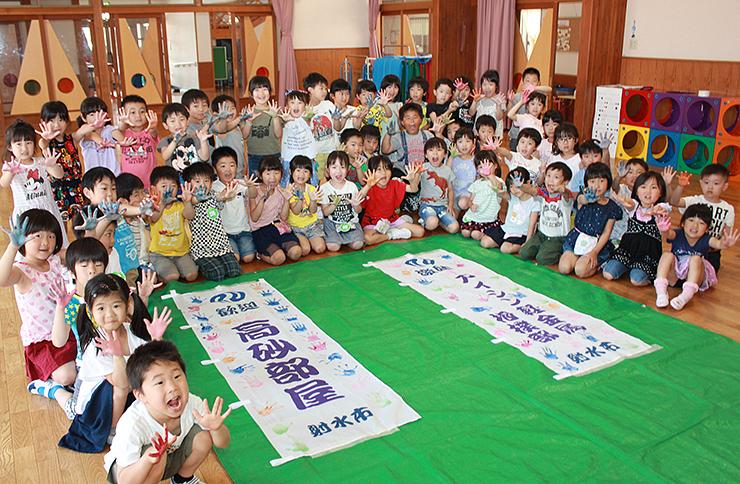 のぼり旗に手形を押し、高砂部屋富山合宿を心待ちにする園児=大門きらら保育園