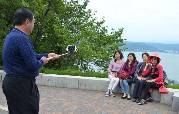 昨年5月に諏訪湖を背に記念撮影する台湾からの観光客。諏訪への外国人観光客は昨年、3年ぶりに増加した