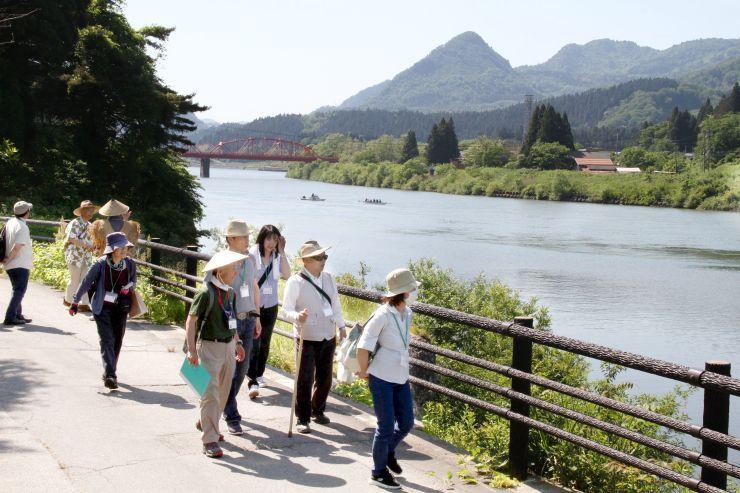舟運が盛んだった阿賀町の川港跡などを町歩きする参加者ら=阿賀町津川
