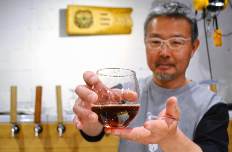 飲み比べてもらうクラフトビール「秩父麦酒」を手にする吉川さん