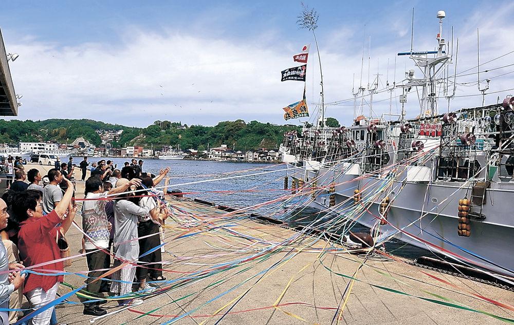 家族に見送られて出港する中型イカ釣り船=能登町小木港