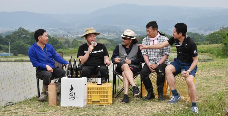 田んぼの横でトークショーをする堀江さん(左から2人目)ら