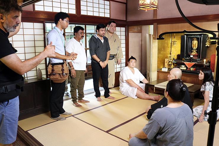 立ち位置やせりふを確認する田代良徳(左から5人目)とインド人スタッフら=内山邸