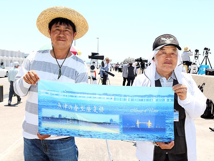 蜃気楼の写真をデザインしたタオルを紹介する野村さん(左)