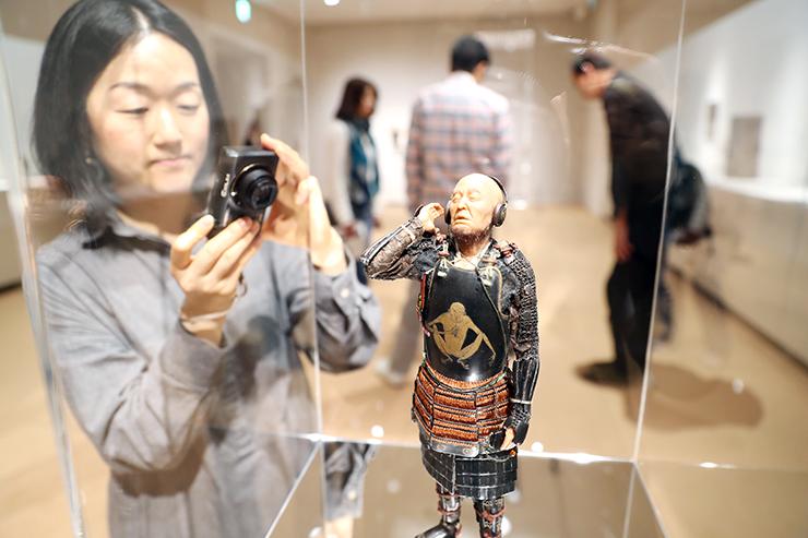 ヘッドホンで音楽を聴く武士の彫刻を写真に収めようとカメラを向ける来場者=森記念秋水美術館
